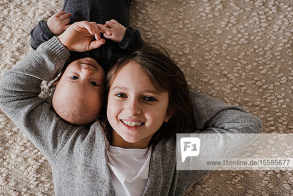 Mädchen liegt Wange an Wange mit kleinem Bruder auf dem Bett  Überkopfporträt