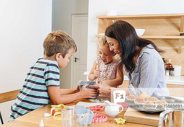 Mother and children baking cupcakes in kitchen