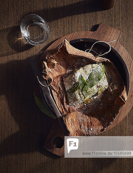 Barramundi baked in paperbark served in wooden bowl  a bush tucker dish using indigenous ingredients