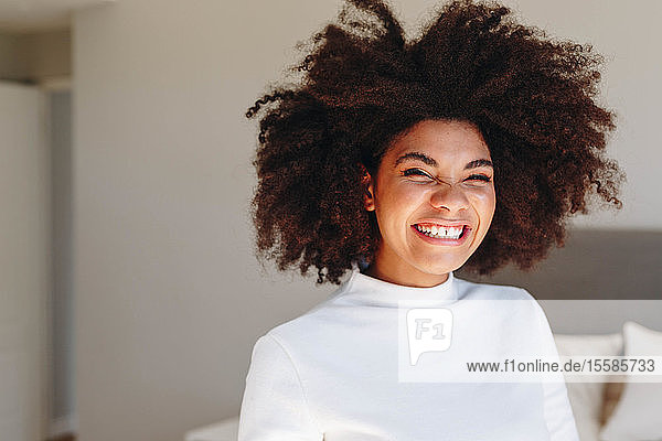 Young woman with afro hairstyle laughing in bedroom  head and shoulder portrait