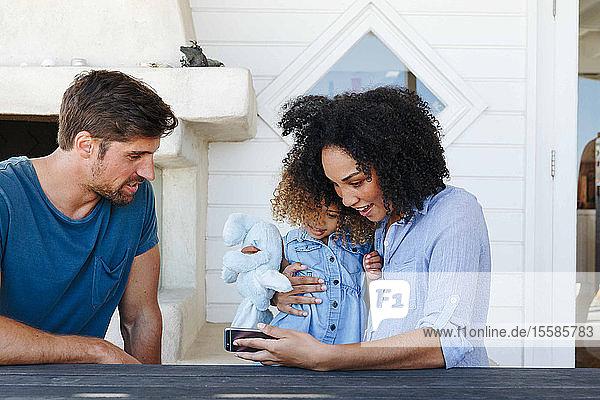 E-Learning für Paare mit Tochter auf Smartphone im Strandhaus