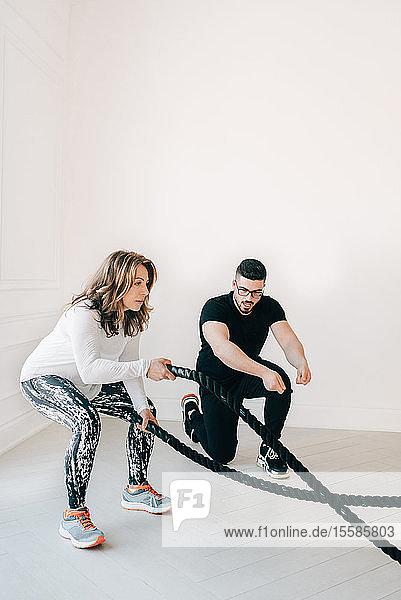 Fitnesstrainerin beobachtet Frau bei der Benutzung des Kampfseils im Studio