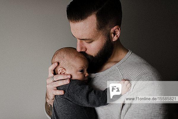Junger Mann küsst kleinen Sohn auf Kopf  Kopf und Schultern