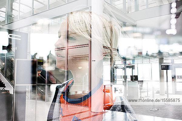 Blondhaariger Junge  der durch ein Flughafenfenster blickt  Kopf und Schultern