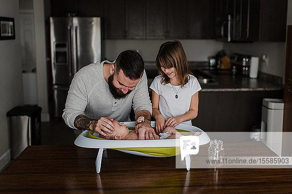 Junger Mann und seine Tochter baden den kleinen Sohn in der Küche