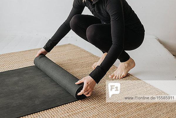 Frau rollt Yogamatte im Studio