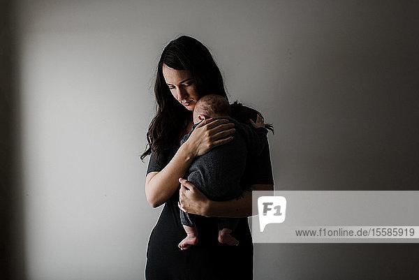 Junge Frau  die einen kleinen Sohn auf dem Arm trägt