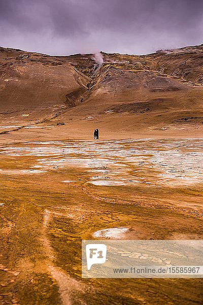 Fernblick von zwei männlichen Touristen  die durch geothermische Landschaft wandern  Namaskard hverir  Myvatn  Island