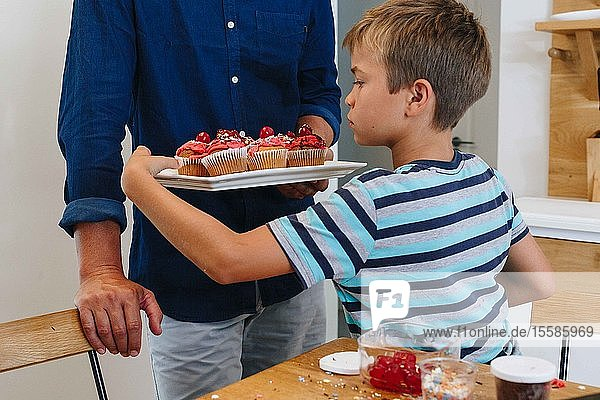 Father serving tray of cupcakes to boy at home