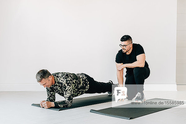Fitness instructor observing man doing plank in studio