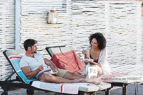 Paar redet und genießt Himbeerkuchen auf Liegestühlen