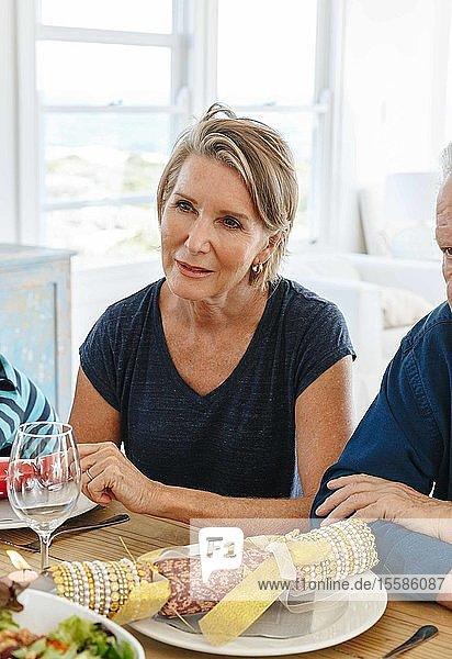 Frau hört aufmerksam am Esstisch in der Hausparty zu