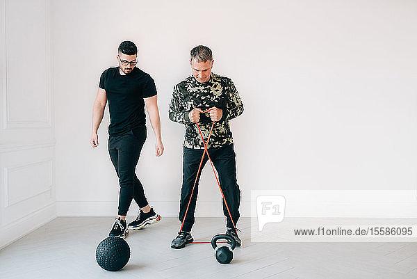 Fitnesstrainer beobachtet Mann  der im Studio ein Widerstandsband benutzt