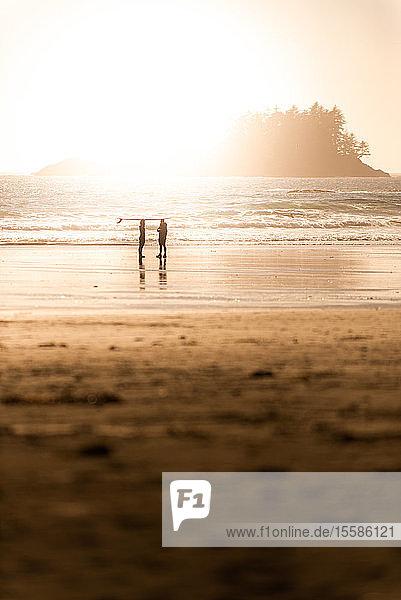 Silhouettenansicht von zwei Surfern am Strand bei Sonnenuntergang  Tofino  Vancouver Island  Kanada