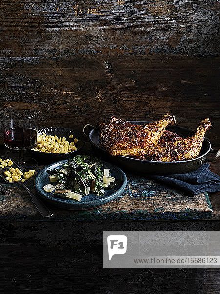 Rustic still life with chipotle chicken  corn and rainbow chard on wooden table