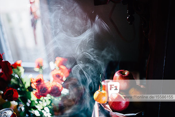 Detail of incense smoke  flowers and fruit at wedding reception