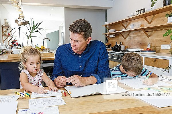 Father helping children with homework at home