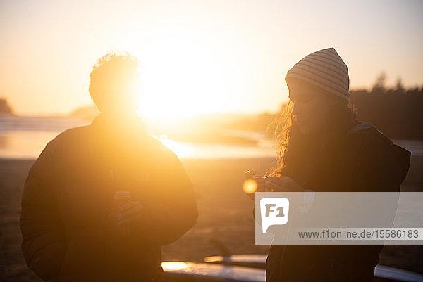 Zwei Freundinnen im mittleren Erwachsenenalter an der Küste bei Sonnenuntergang  Tofino  Vancouver Island  Kanada