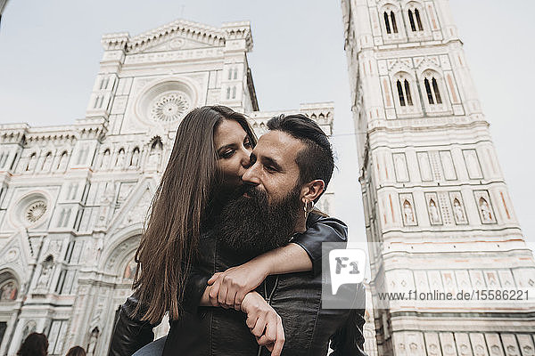 Couple playing piggyback ride and kissing  Santa Maria del Fiore  Firenze  Toscana  Italy