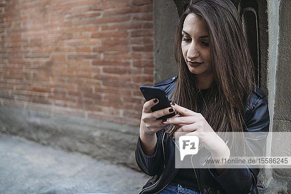Frau benutzt Smartphone auf Stufen