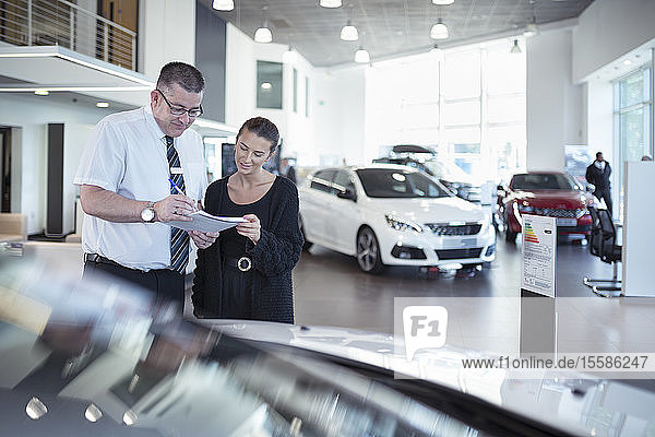 Salesman discussing contract with customer in car dealership