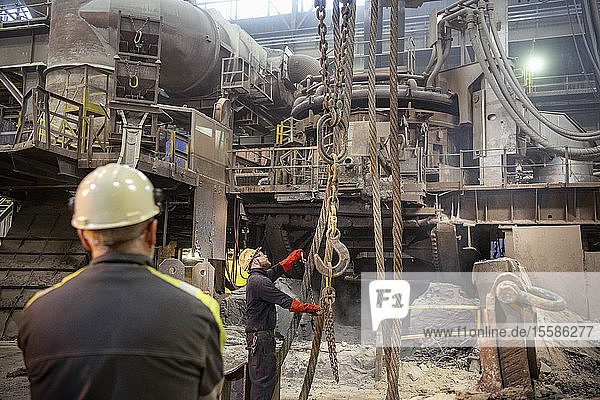 Workers arranging crane lines in steelworks