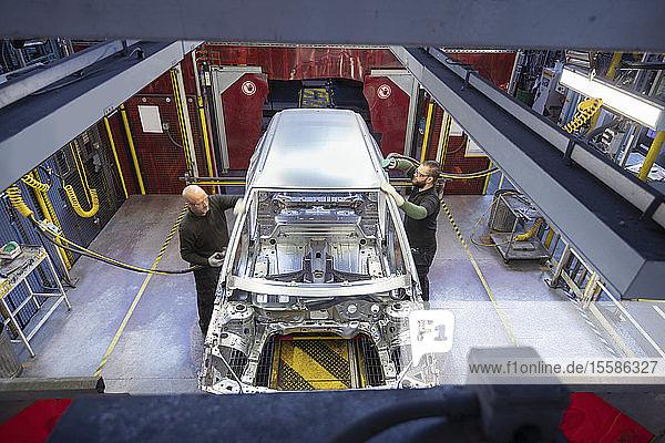 Arbeiter polieren Autokarosserien am Fließband in einer Autofabrik