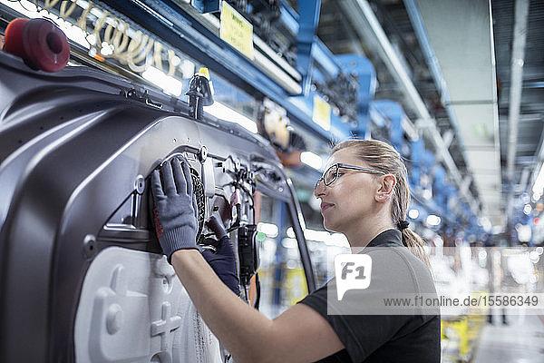 Arbeitnehmerin bei der Montage von Autotüren am Fließband in einer Autofabrik