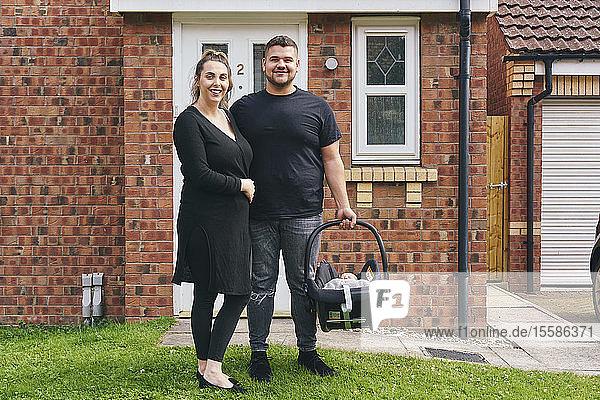Paar trägt Baby in Wiege vor dem Haus