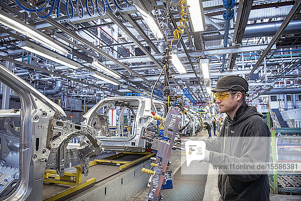 Car worker fitting parts on production line in car factory