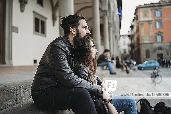 Mann umarmt Frau von hinten auf Stufen