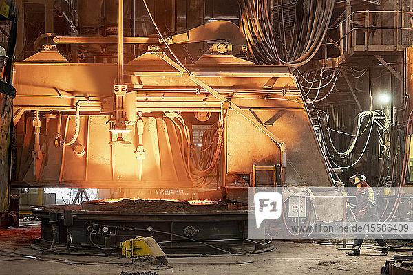 Stahlarbeiter bei der Probenentnahme am Ofen im Stahlwerk