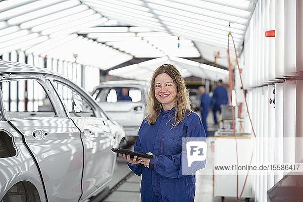 Porträt einer Arbeitnehmerin mit digitalem Tablett im Lackierkontrollbereich einer Autofabrik