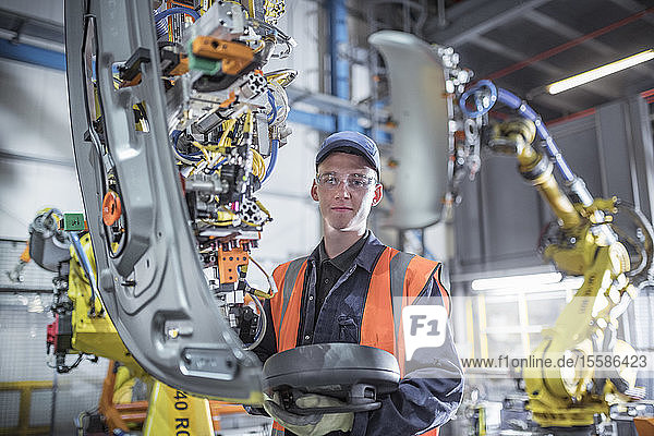 Porträt eines auszubildenden Ingenieurs  der Roboter in einer Autofabrik programmiert