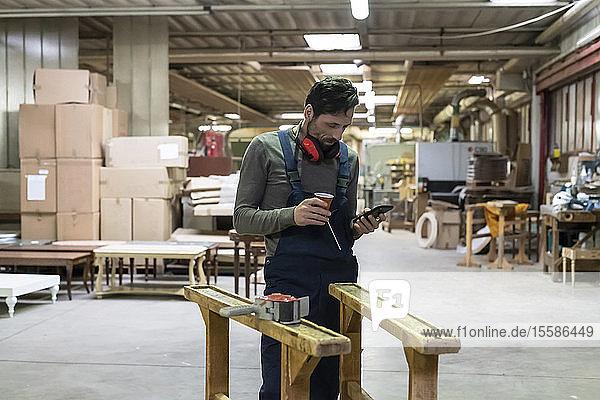 Arbeiter benutzt Smartphone während der Kaffeepause in der Fabrik