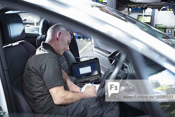 Ingenieur mit Computer zur Überprüfung der Autoelektronik im Autowerkstatt