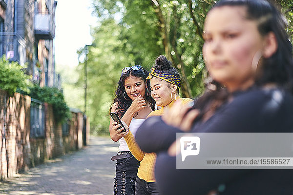 Young woman with teenage sisters looking at smartphone by park