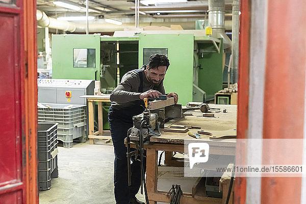 Schreiner schleift hölzernes Möbelbein in der Fabrik