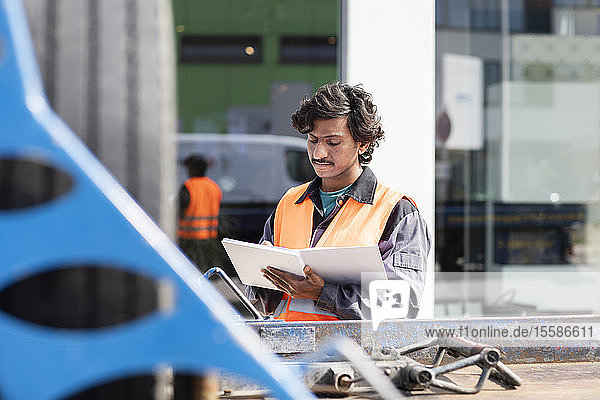 Male engineer on construction site writing in notebook