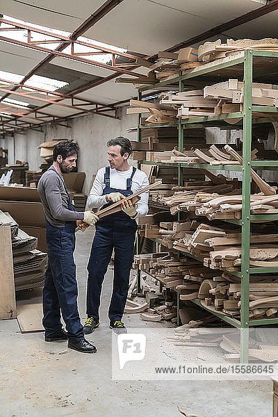 Arbeiter sprechen über hölzerne Möbelbeine in der Fabrik