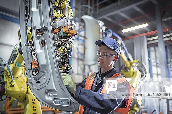 Auszubildender Ingenieur beim Justieren eines Roboters in einer Autofabrik