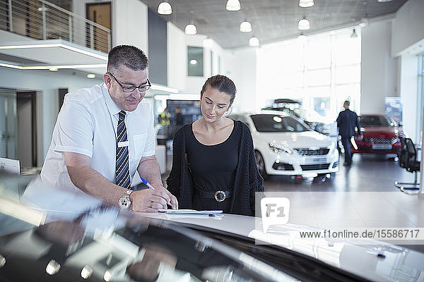 Salesman showing literature to customer in car dealership