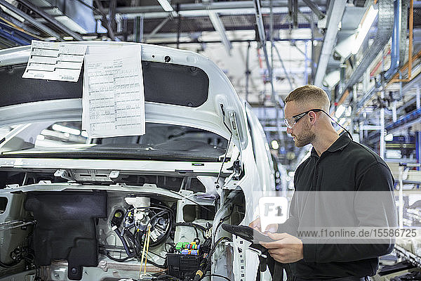 Engineer with digital tablet on production line in car factory