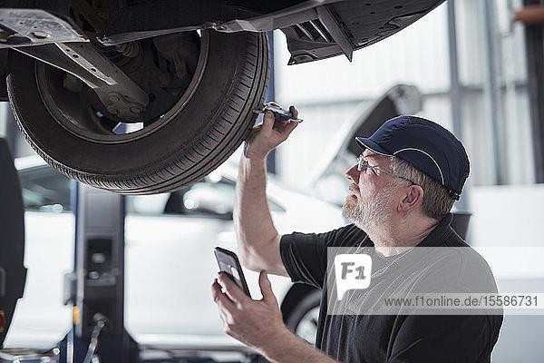 Ingenieur prüft Autoreifen während des Service im Autowerkstatt