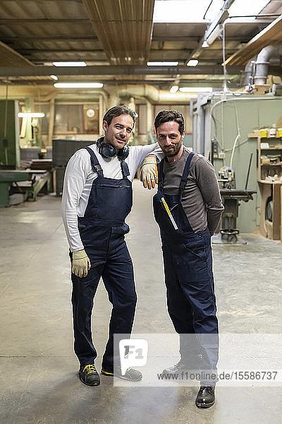 Arbeiter ruht Arm auf der Schulter eines Kollegen in der Fabrik
