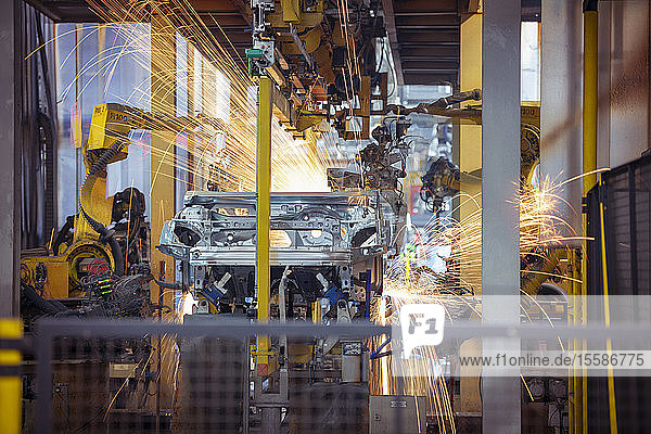 Robots welding steel car body in car factory