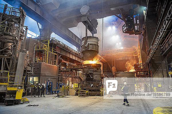 Stahlarbeiter gießen geschmolzenen Stahl in den Schmelzbetrieb eines Stahlwerks
