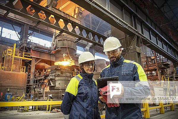 Männliche und weibliche Stahlarbeiter verwenden digitale Tabletts während des Stahlgießens in Stahlwerken