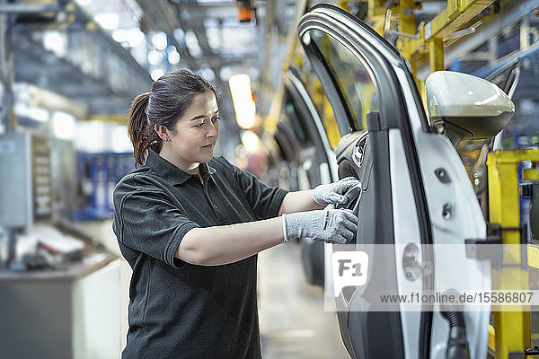 Female apprentice engineer assembling car doors in car factory