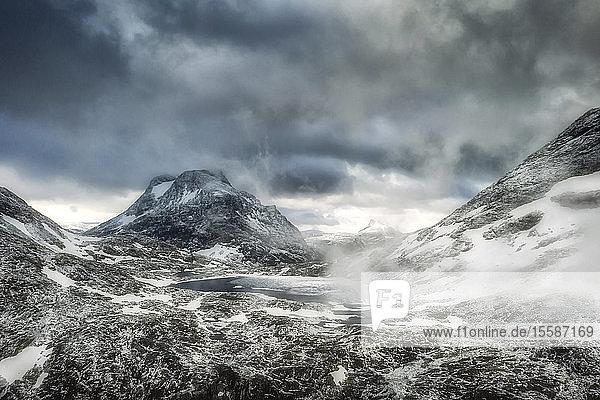 Storm clouds over Olaskarsvatnet lake at feet of the snowcapped Olaskarstind mountain  Venjesdalen valley  Andalsnes  Norway  Scandinavia